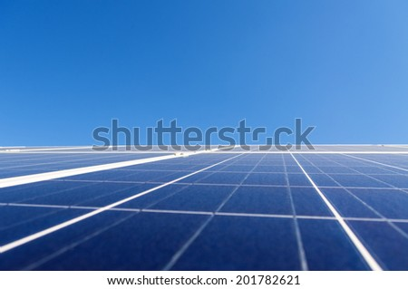 Solar photovoltaic panel over clear blue sky - stock photo