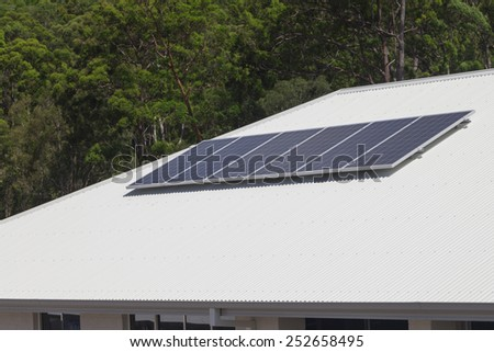 Solar photovoltaic panels installed on aluminium roof - stock photo