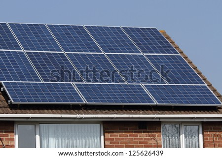 Solar photovoltaic panels mounted on a tiled house roof