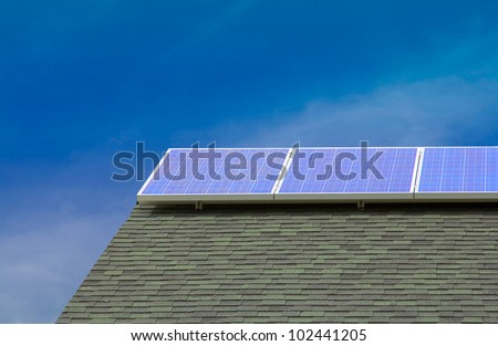 Solar photovoltaic panels on the rood of a house with a clear sky background