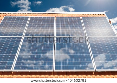 Solar (photovoltaic) panels producing electricity on a house roof during a sunny day - stock photo