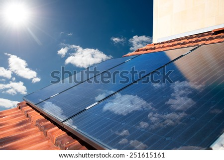 Solar photovoltaic (PV) panels producing electricity on a sunny day - stock photo