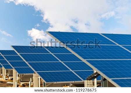 Solar photovoltaics panels field for renewable energy production with blue sky and clouds - stock photo
