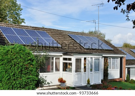 Solar power installed on roof of small bungalow - stock photo