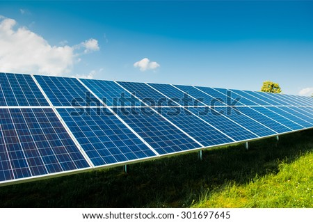 Solar power panels on green field with blue sky and copy space and text area - stock photo