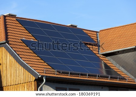 Solar power photovoltaic energy panels fitted to new house roof producing electricity from sunlight