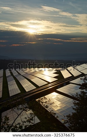 Solar power plant at sunset amongst forests. The smoking smokestack and forested mountains fading into the misty haze and smog in the background. - stock photo