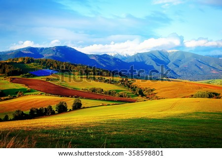 Solar power plant in the mountains on meadow. Beautiful landscape scenery - stock photo