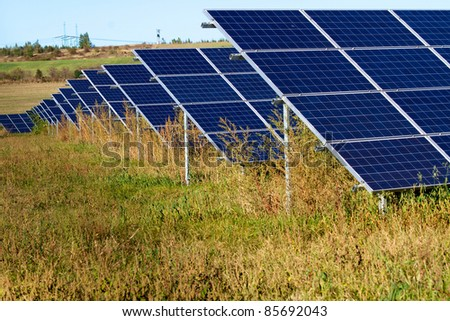 Solar power plant on the field with poles - stock photo