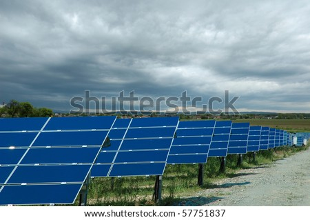 Solar power plant with cloudy sky - stock photo