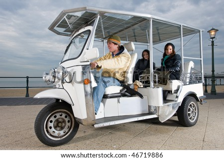 Solar powered tuc tuc at the beach, picking up a fare - stock photo