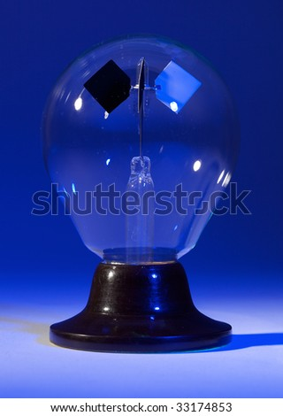 Solar spinner with blue background and spotlighted lighted base. - stock photo