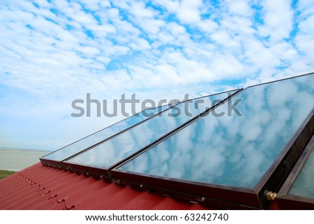 Solar system on the red house roof - stock photo