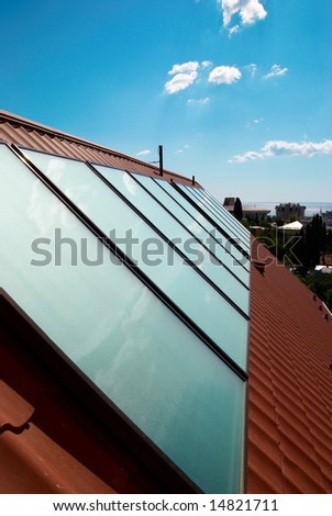 Solar water heating system (geliosystem) on the house roof. - stock photo