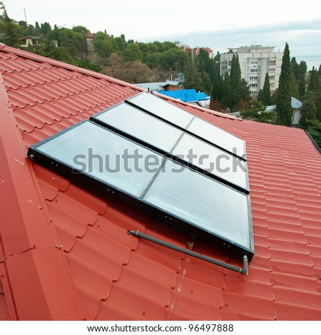 Solar water heating system (geliosystem) on the red house roof. - stock photo