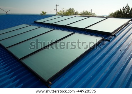 Solar water heating system on the house roof. - stock photo