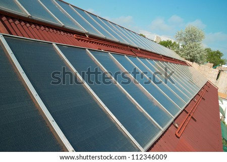 Solar water heating system on the red roof. Gelio panels. - stock photo