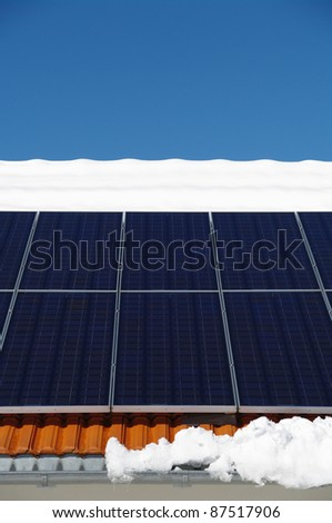 solarcells on a winter roof with snow... - stock photo