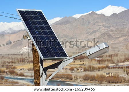 solarcells on a winter roof with snow mountain - stock photo