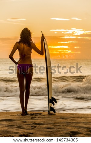Solarised style photograph rear view of beautiful sexy young woman surfer girl in bikini with white surfboard on a beach at sunset or sunrise - stock photo