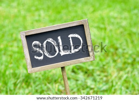 Sold - chalkboard on green grass background - stock photo
