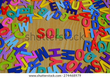 SOLD Colorful conceptual words on alphabet letters with Background texture of wood.  Slightly defocused and close-up shot