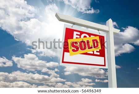 Sold For Sale Real Estate Sign over Clouds and Blue Sky with Sun Rays. - stock photo