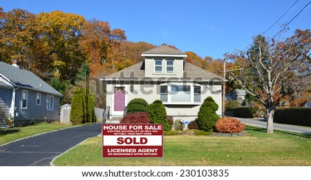 Sold Real Estate (another success let us help you buy sell your next home) sign on front yard lawn of suburban bungalow style home residential neighborhood clear blue sky USA - stock photo