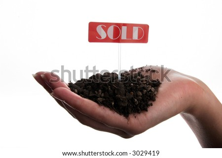 Sold sign and soil in hand isolated on white background - stock photo