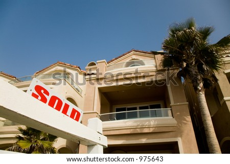 Sold sign in front of the luxury house in the suburbs. - stock photo