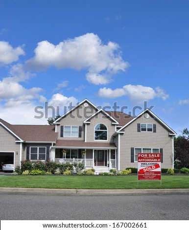 Sold Suburban McMansion Home Landscaped with Flowers Residential Neighborhood USA Blue Sky Clouds. Real Estate Sign (Another success let us help you buy / sell your next home) - stock photo