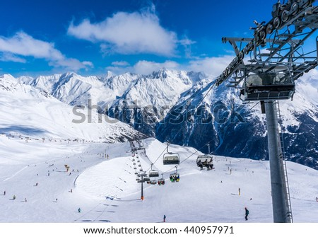 SOLDEN, AUSTRIA - 9 MARCH 2016: Skiers and double chairlift in Alpine ski resort in Solden - stock photo