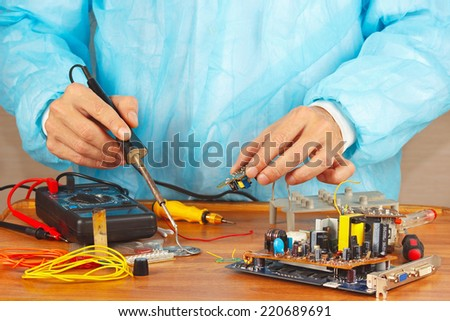 Soldering electronic components of device in the service workshop - stock photo