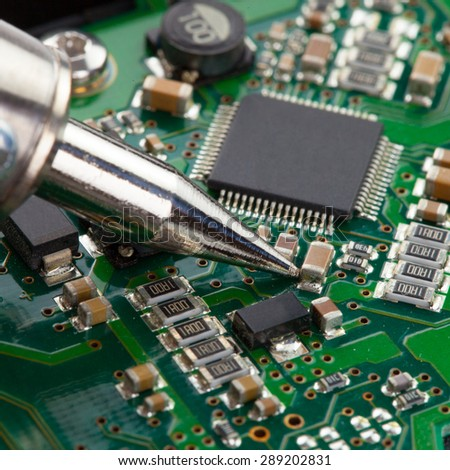 Soldering iron with microcircuit - close up shot - stock photo