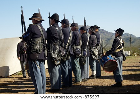 Solders at attention in a civil war encampment.