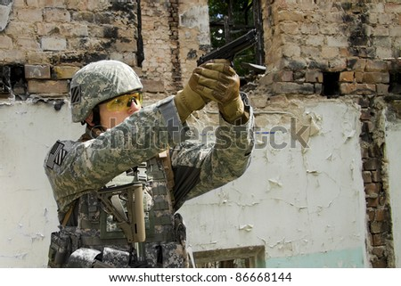 Soldier aiming his pistol on the ruins