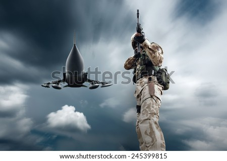 Soldier and military airplane at flying under sky - stock photo