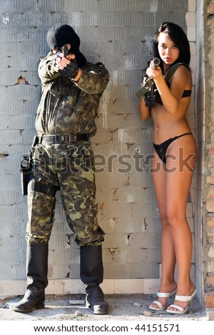 Soldier and sexy woman in underclothes with arms - stock photo