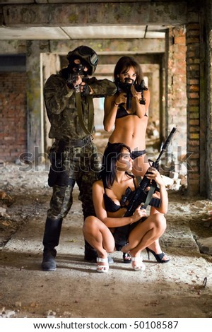 Soldier and two sexy women with rifles in the abandoned building