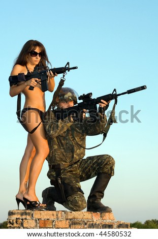 Soldier and woman in bikini aiming on the brick wall - stock photo