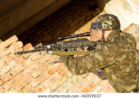 Soldier assaulting near the red brick wall - stock photo