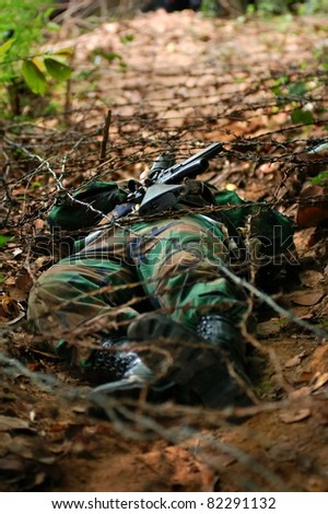 soldier carrying m16 crawling under barb  in combat training - stock photo
