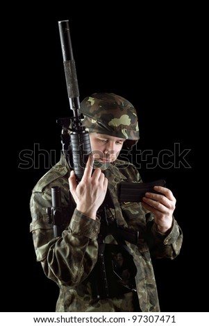 Soldier changing magazine of m16 in studio. Isolated