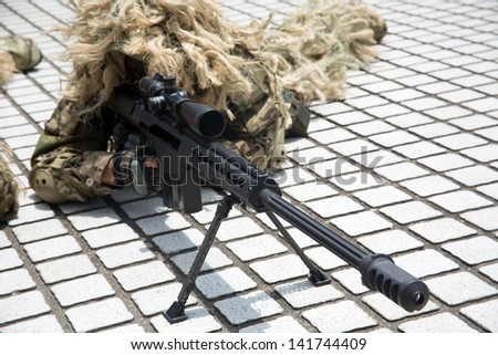 soldier dressed in uniform aims his rifle while on duty - stock photo