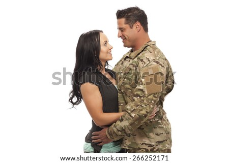 Soldier embracing his wife against white background - stock photo
