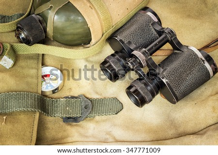Soldier flask (canteen) in decay cloth winding and classic binoculars with compass on rucksack - stock photo