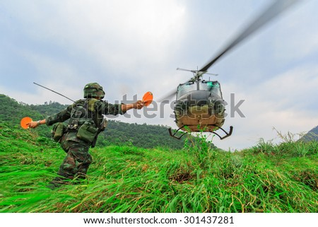 Soldier give landing signal for helicopter on mountain