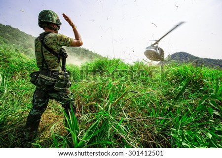 Soldier give landing signal for helicopter with hard wind