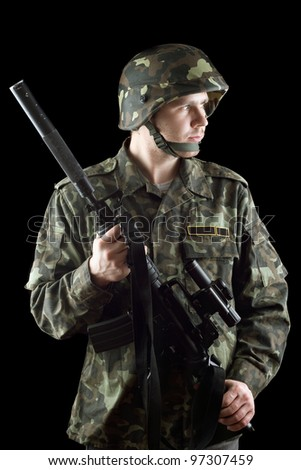 Soldier grasping a gun in studio. Isolated - stock photo