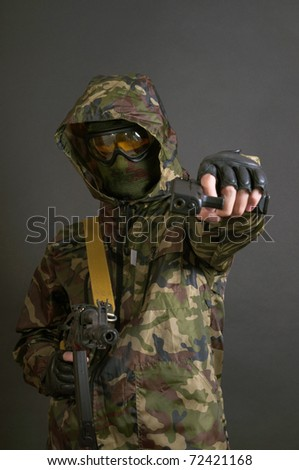 Soldier holding a machine gun AK-47 and pistol - stock photo